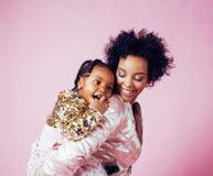 Молодая милая Афро-американская мать при маленькая милая дочь обнимая, счастливый усмехаться на розовой предпосылке, образе жизни Стоковые Изображения