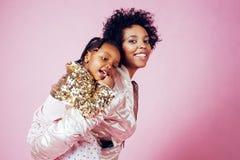 Молодая милая Афро-американская мать при маленькая милая дочь обнимая, счастливый усмехаться на розовой предпосылке, образе жизни Стоковое Фото