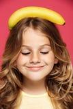 Молодая милая девушка держа банан на голове над розовой предпосылкой стоковые фотографии rf