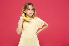 Молодая милая девушка держа банан любит телефон над розовой предпосылкой стоковые изображения rf