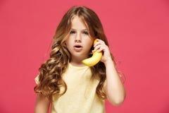 Молодая милая девушка держа банан любит телефон над розовой предпосылкой стоковая фотография rf