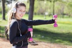 Молодая милая девушка делая тренировку и ход в парке стоковое изображение rf