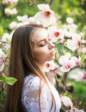 Молодая милая девушка ослабляет в красивом саде Фантастические розовые магнолии Стоковые Фотографии RF