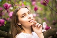 Молодая милая девушка ослабляет в красивом саде Фантастические розовые магнолии Стоковая Фотография