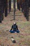 Молодая милая девушка сидит в положении лотоса в природе в conife Стоковая Фотография
