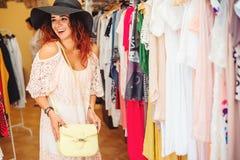 Молодая милая женщина в черной шляпе пробуя на новой сумке в магазине одежды сеть универсалии времени шаблона покупкы страницы пр Стоковые Фото