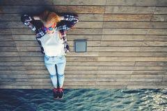 Молодая милая женщина лежа на деревянной моле наслаждаясь солнечностью Стоковое фото RF