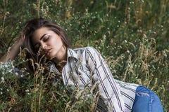 Молодая милая женщина лежа на траве Естественные счастье, потеха и сработанность Стоковое Изображение