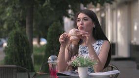Молодая милая женщина есть очень вкусный круассан в кафе, видеоматериал