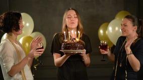 Молодая милая женщина делает желание и дует вне свечи на шоколадном торте, 2 усмехаясь дамы Clinking стекла акции видеоматериалы