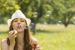 Молодая милая женщина имеет потеху с пузырем в парке лета Стоковое фото RF