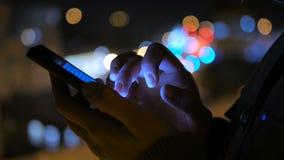 Молодая милая женщина используя smartphone в городе на ноче Стоковые Изображения RF