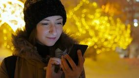 Молодая милая женщина используя smartphone в городе на ноче Стоковое Изображение RF