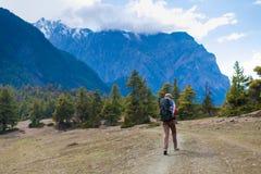 Молодая милая женщина нося красные горы следа рюкзака куртки Взгляд ландшафта пути утесов горы Азии Trekking Стоковые Фото