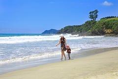 Молодая милая женщина при ее дочь гуляя вдоль песчаного пляжа Стоковые Фото