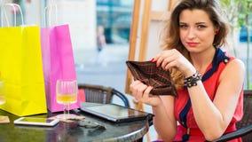 Молодая милая женщина при пусковая площадка держа пустой бумажник. Она распологает в кафе. Стоковое Фото