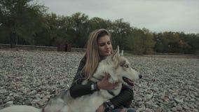 Молодая милая женщина при собака сибирской лайки сидя на речном береге сток-видео