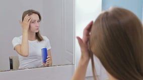 Молодая милая женщина расчесывая ее волосы перед зеркалом акции видеоматериалы