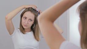 Молодая милая женщина расчесывая ее волосы перед зеркалом сток-видео