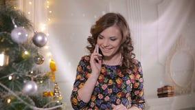 Молодая милая красивая девушка говорит мобильным телефоном около рождественской елки отпразднуйте носить santa мати шлемов дочи р акции видеоматериалы