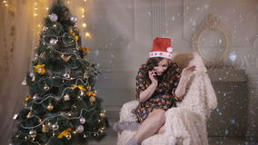Молодая милая красивая девушка говорит мобильным телефоном около рождественской елки отпразднуйте носить santa мати шлемов дочи р сток-видео
