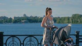 Молодая милая мать отбрасывает прогулочную коляску на предпосылке берега реки акции видеоматериалы