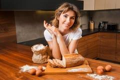 Молодая милая домохозяйка в кухне около tableboard стоковое фото