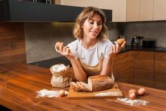Молодая милая домохозяйка в кухне около tableboard стоковая фотография rf