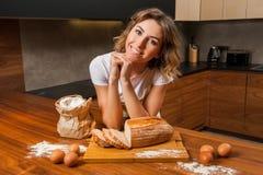Молодая милая домохозяйка в кухне около tableboard стоковое изображение