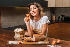 Молодая милая домохозяйка в кухне около tableboard стоковые изображения