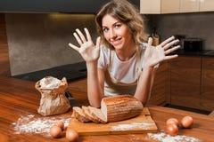 Молодая милая домохозяйка в кухне с мукой на руках стоковое изображение rf