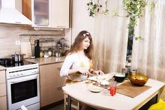 Молодая милая домохозяйка женщины варя на кухне, расквартировывает интерьер, концепцию людей образа жизни Стоковое фото RF