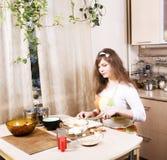 Молодая милая домохозяйка женщины варя на кухне, расквартировывает интерьер, концепцию людей образа жизни Стоковые Изображения