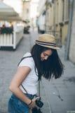 Молодая милая прогулка фотографа женщины старой улицей города с ретро камерой Стоковое фото RF