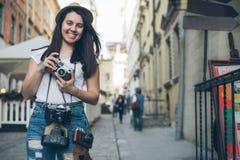 Молодая милая прогулка фотографа женщины старой улицей города с ретро камерой Стоковая Фотография RF