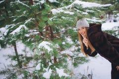 Молодая модельная прогулка девушки в лесе зимы Стоковое фото RF