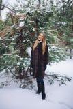 Молодая модельная прогулка девушки в лесе зимы Стоковое Изображение
