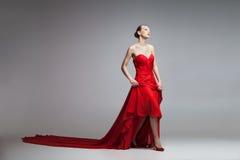 Молодая модель в длинном красном платье Стоковое Фото