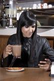 Молодая модель на cofeeshop отправляя СМС на телефоне Стоковое Изображение