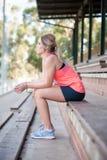 Молодая модель feamle сидела в пустом стадионе Стоковое Изображение