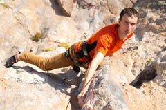 Молодая мужская смертная казнь через повешение альпиниста скалой Стоковые Изображения RF