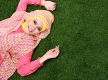 Молодая мусульманская девушка лежа на траве Стоковое фото RF