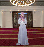 Молодая мусульманская девушка молит в мечети Стоковая Фотография