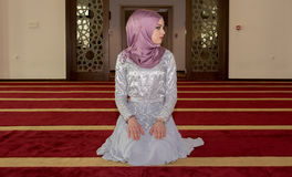 Молодая мусульманская девушка молит в мечети Стоковое Фото