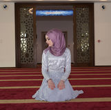 Молодая мусульманская девушка молит в мечети Стоковые Изображения
