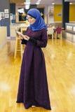 Молодая мусульманская женщина с электронной таблеткой в ее руках Стоковая Фотография RF