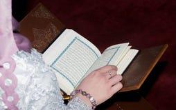 Молодая мусульманская женщина читая Koran Стоковая Фотография