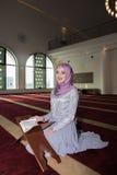 Молодая мусульманская женщина читая Koran Стоковое Изображение