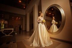 Молодая невеста в платье свадьбы смотря большое зеркало Стоковые Фотографии RF