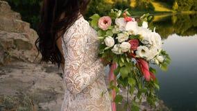Молодая невеста держа букет на речном береге, конец-вверх акции видеоматериалы